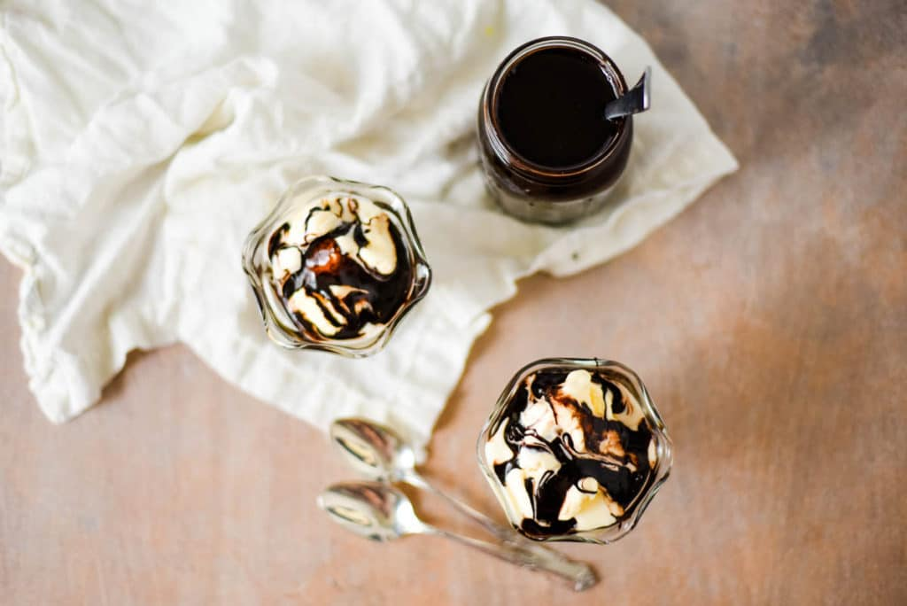 overhead view of two ice cream dishes with vanilla ice cream and hot fudge sauce